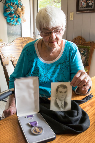 Fran Nutter displays her older brother Bernard's picture and his Purple Heart.