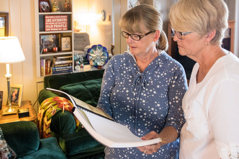 Deanne Grantham (left) and her sister Pat Albright of Lake City, Iowa, review information supplied about their uncle from the U.S. Navy.